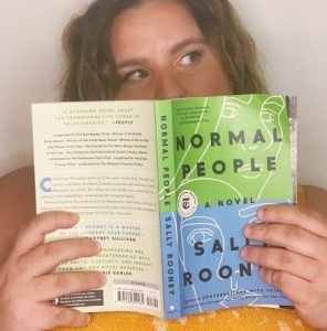 """Katie, a white woman, holds a copy of """"Normal People"""" by Sally Rooney."""